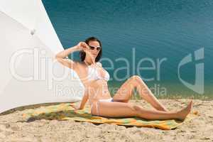 Summer beach young woman sunbathing in bikini