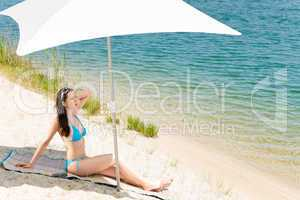 Summer beach woman blue bikini under parasol