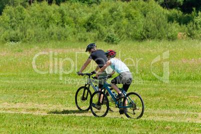 Sport mountain couple biking downhill sunny meadows