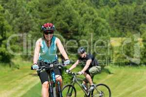 Sport mountain couple biking uphill sunny meadows