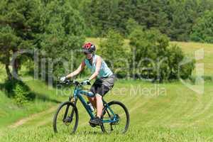 Sport mountain girl biking uphill sunny meadows