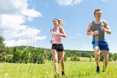 Sportive young couple jogging meadows sunny summer