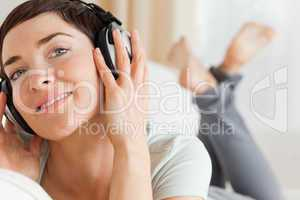 Close up of a smiling brunette listening to music