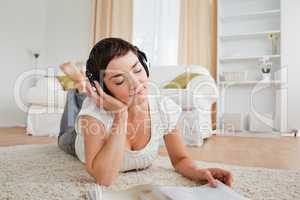 Cute woman with a magazine enjoying some music