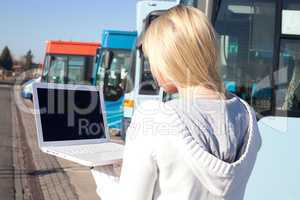 young blond woman with laptop in front of busses