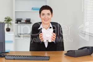 Smiling office worker holding a piggybank