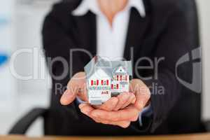 Feminine hands holding a miniature house