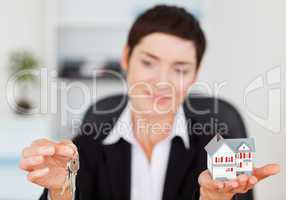 Businesswoman showing a miniature house and a key