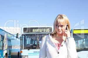 young blond woman with a cell phone in front of a bus