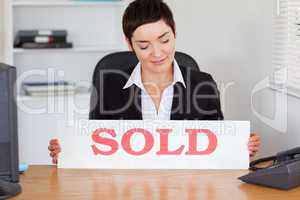 Real estate agent looking at a sold panel