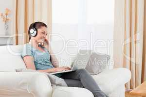 Attractive woman with headphones relaxing with her laptop while