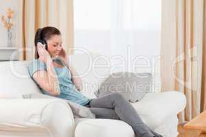Gorgeous woman relaxing with headphones while sitting on a sofa