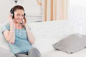 Attractive woman relaxing with headphones while sitting on a sof
