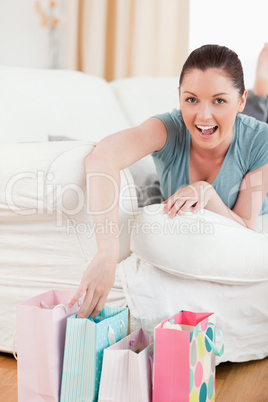 Attractive woman touching her shopping bags while lying on a sof