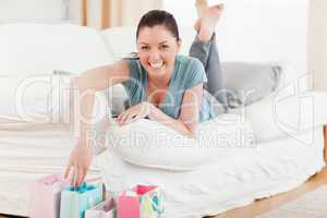 Good looking woman touching her shopping bags while lying on a s