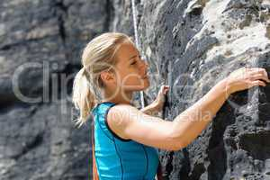 Rock climbing blond woman on rope