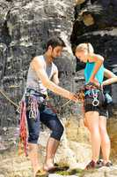 Rock climbing man showing woman rope knot