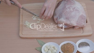 Slicing garlic into thin strips on wooden chopping board