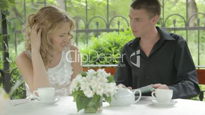 Romantic young couple sitting outdoors in summer cafe, smiling, flirting