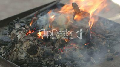 Blacksmith turning bronze already charred coffee maker on live coals