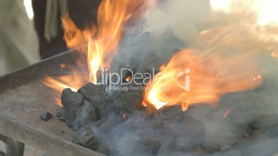 Close-up of fire flames from live coals blacksmith forge outdoors.