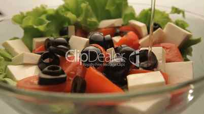 Pour vegetable salad with olive oil