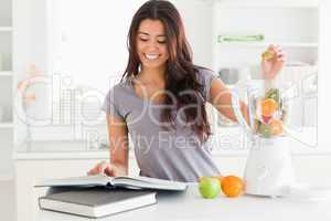 Charming woman consulting a notebook while filling a blender wit