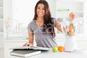 Beautiful woman consulting a notebook while filling a blender wi