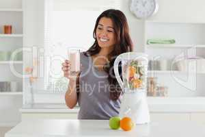 Attractive woman using a blender while holding a drink