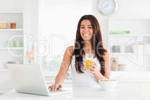 Beautiful woman relaxing with her laptop while holding a glass o