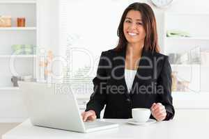 Attractive woman in suit enjoying a cup of coffee while relaxing