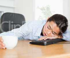 Frontal view of a beautiful woman sleeping on a keyboard while h