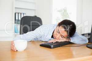 Frontal view of a pretty woman sleeping on a keyboard while hold