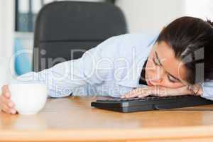 Frontal view of a good looking woman sleeping on a keyboard whil