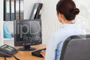 View from behind of a beautiful woman typing on a keyboard while
