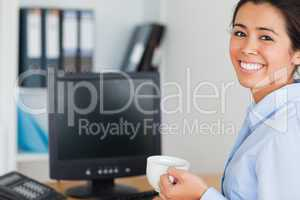 Good looking woman holding a cup of coffee while sitting