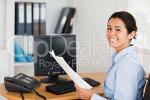 Pretty woman holding a sheet of paper and posing while sitting