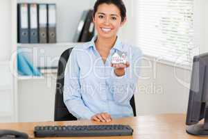 Good looking woman holding a miniature house while looking at th