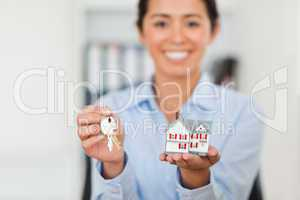 Attractive woman holding keys and a miniature house while lookin