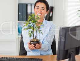 Attractive woman holding a plant while looking at the camera
