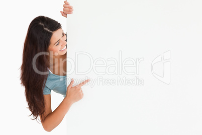 Gorgeous woman pointing at a board