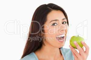 Lovely woman eating a green apple