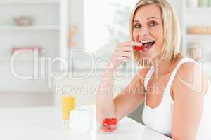 Young woman sitting at table eats strawberries