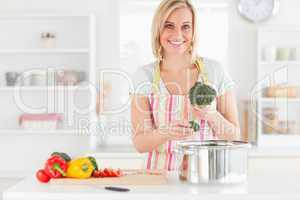 Woman cooking broccoli looks into the camera