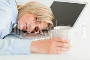 Gorgeous woman sleeping on her laptop with cup of coffee in hand
