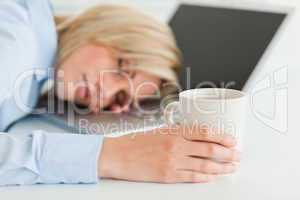 Gorgeous woman sleeping on her laptop holding cup of coffee