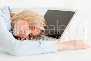Cute blonde woman sleeping on her notebook holding cup of coffee