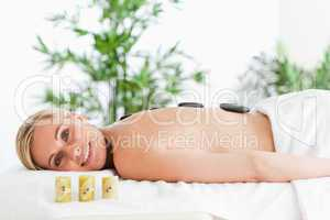 Blonde smiling woman having a stone therapy