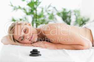 Good looking blonde woman lying on a lounger with eyes closed