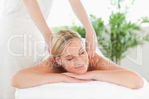 Close up of a smiling woman relaxing on a lounger enjoys a massa